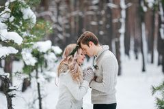 Bride and groom in beige knitted pullovers in snowy forest. Newlyweds is touching foreheads. Winter wedding royalty free stock photos