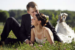 Bride and Groom being romantic. A portrait of a bride in a traditional white wedding dress. She is lying with her new husband in a field being romnantic Royalty Free Stock Photography