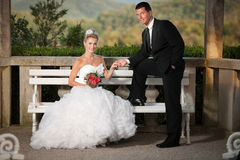 Bride and groom on a bench in a park Stock Photography