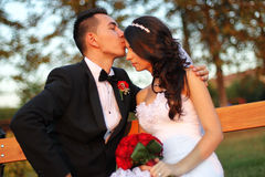 Bride and groom on a bench with a red flower bouquet at sunset. Lovely day Royalty Free Stock Photography