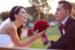 Bride and groom on a bench with a red flower bouquet at sunset Stock Image