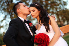 Bride and groom on a bench with a red flower bouquet at sunset Stock Photos