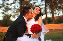 Bride and groom on a bench with a red flower bouquet at sunset Stock Images