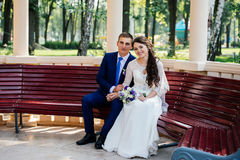 Bride and groom on a bench Royalty Free Stock Images