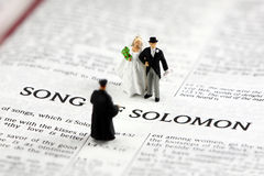Bride and groom on bible. Concept image of a miniature bride and groom getting married by a priest on the open pages of a bible. The bible is open to the Song of stock image
