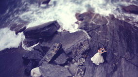 Bride and groom on a big rock near the sea. Groom and bride dancing on a big rock near the sea Royalty Free Stock Photo