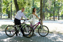 Bride groom and bikes. Beautiful bride and groom riding on the bikes Royalty Free Stock Photography