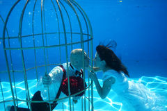 Bride and groom and a birdcage underwater pool water dive Stock Images
