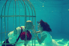 Bride and groom and a birdcage underwater pool water dive Royalty Free Stock Images