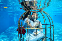 Bride and groom and a birdcage underwater pool water dive Stock Photo