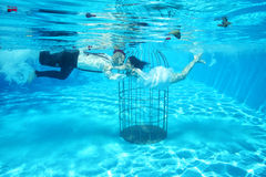Bride and groom and a birdcage underwater pool water dive Royalty Free Stock Photography