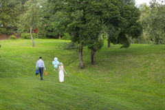 Bride and groom with blue balloons and picnic basket near apple trees Stock Photo