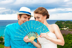 Bride and groom with blue fan with a tropical beach in the backg Royalty Free Stock Image