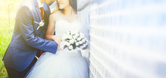 Bride and groom in a blue suit embracing near a white brick wall Royalty Free Stock Photography