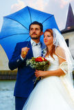 The bride and groom with blue umbrella in a historical church. Stock Photo