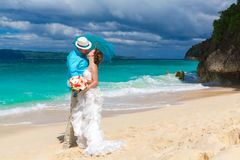 Bride and groom with blue umbrella kiss on the tropical coast Stock Photography