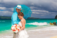 Bride and groom with blue umbrella and wedding bouquets on Stock Image