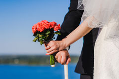 Bride, groom, bouquet against background of river Royalty Free Stock Image