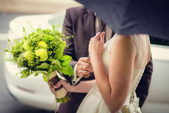 Bride and groom with a bouquet of flowers under the umbrella Royalty Free Stock Photography