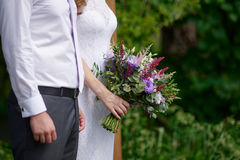 Bride and groom with a bouquet of flowers on the walk Royalty Free Stock Photos
