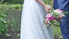 The bride and groom with a bouquet goes stock footage