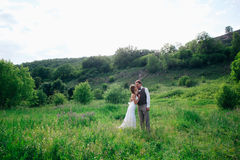 The bride and groom with a bouquet in the grass against the background mountain landscape Royalty Free Stock Photo
