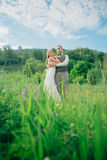 The bride and groom with a bouquet in the grass against the background mountain landscape Royalty Free Stock Image