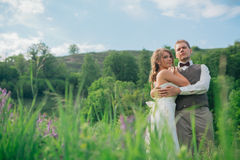 The bride and groom with a bouquet in the grass against the background mountain landscape Royalty Free Stock Images