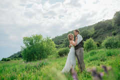 The bride and groom with a bouquet in the grass against the background mountain landscape Stock Photography
