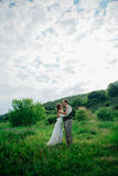 The bride and groom with a bouquet in the grass against the background mountain landscape Royalty Free Stock Photos