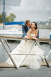 Bride and groom with a bouquet posing on a background pier with yachts Royalty Free Stock Image