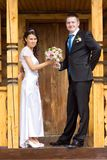 Bride and groom with a bouquet in a wooden porch Royalty Free Stock Photography