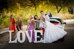 bride and groom and bride's girlfriends on the road Royalty Free Stock Images