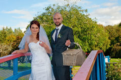 Bride and groom on bridge. Happy bride and groom in a park standing on bridge over a lake, groom holding picnic basket Stock Images