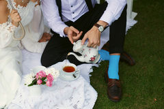Bride and groom in bright clothes on the green grass Stock Photo