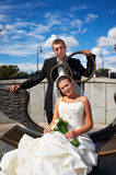Bride and groom on bronze bench Stock Photo