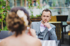 Bride and groom in a cafe outdoor. A men looks at a woman. Focus on the guy. Groom in a suit and a bow tie royalty free stock photos