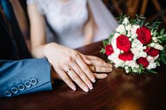 Bride and groom in a cafe. wedding bouquet of roses on a wooden table in a restaurant, bride and groom hold each other`s royalty free stock photography