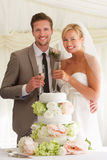 Bride And Groom With Cake Drinking Champagne At Reception. Smiling To Camera Stock Images