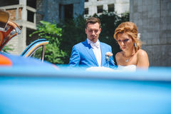 Bride and Groom at Car. Bride and groom at blue old car Royalty Free Stock Photography