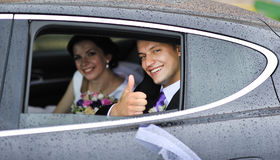 Bride and groom in a car Stock Images