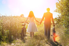 Bride and groom carry bikes Royalty Free Stock Photos