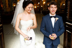 Bride and groom carry sweets for their guests Stock Photos