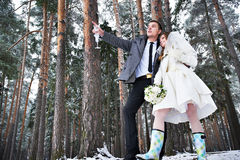 Bride and groom with champagne glasses in winter forest Royalty Free Stock Photos