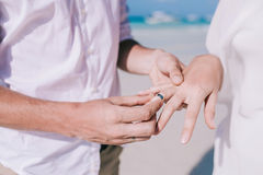 Bride and groom change rings at their wedding on the white sand beach. Stock Photo