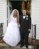 Bride and groom on the church steps Stock Photos