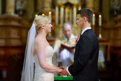 Bride and groom at the church. During a wedding ceremony Stock Photography