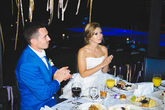 Bride and Groom Clapping Hands. At table Stock Images