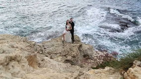 Bride and groom on a cliff above the ocean stock video