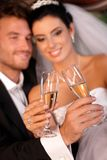 Bride and groom clinking glasses Royalty Free Stock Photography